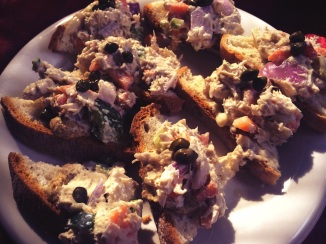 "Vegan ""tuna"" salad on gluten free crostini, garnished with capers."